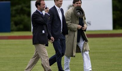 Britain's Prince Harry (center) walks across the polo field with Peter Brant (right), founder of the Greenwich Polo Club, and an unidentified man before the Sentebale Royal Salute Polo Cup charity match in Greenwich, Conn., on Wednesday, May 15, 2103. (AP Photo/Craig Ruttle)