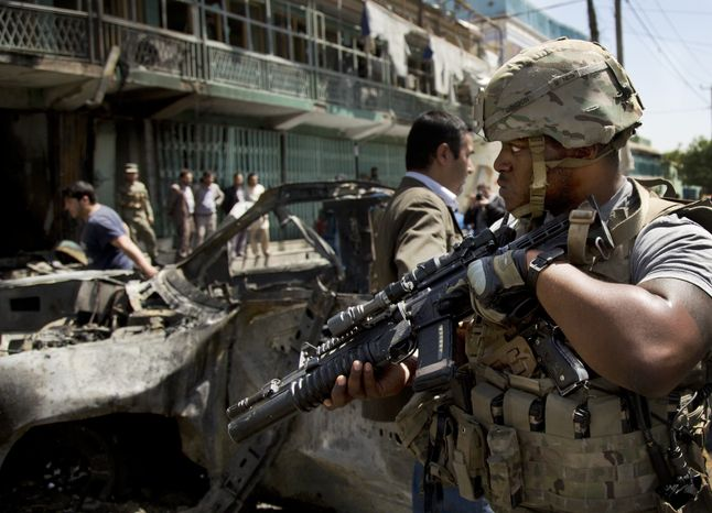 A U.S. soldier arrives to the scene where a suicide car bomber attacked a NATO convoy in Kabul, Afghanistan, Thursday, May 16, 2013. (AP Photo/Anja Niedringhaus)