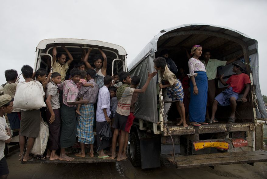 A Rohingya boy, center left, touches a face of a another boy as a truck leave a camp for displaced Rohingya people in Sittwe, northwestern Rakhine State, Myanmar, Thursday, May 16, 2013. Members of the displaced Rohingya minority started to evacuate for safer shelters ahead of the arrival of Cyclone Mahasen. (AP Photo/Gemunu Amarasinghe)