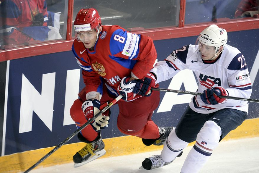 Russia's Alexander Ovechkin, left, vies for the puck with USA's Matt Hunwick during the 2013 Ice Hockey IIHF World Championships Group B Quarterfinal match Russia vs USA in Helsinki, Finland on Thursday May 16, 2013. (AP Photo/LEHTIKUVA / Martti Kainulainen)