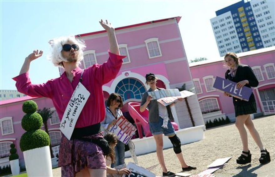 Demonstrators protest in front of the Barbie Dream House in Berlin Thursday, May 16, 2013. (AP Photo/dpa, Jens Kalaene)