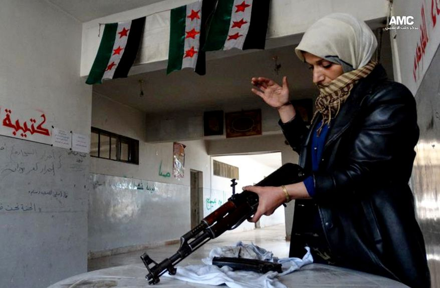 **FILE** This citizen journalism image from May 14, 2013, provided by Aleppo Media Center and authenticated based on its contents and other AP reporting, shows the mother of a Syrian rebel cleaning a rifle in Aleppo, Syria. (Associated Press/Aleppo Media Center AMC)