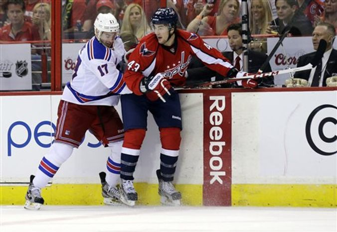 New York Rangers defenseman John Moore (17) and Washington Capitals right wing Tom Wilson (43) collide in the second period of Game 5 first-round NHL Stanley Cup playoff hockey series, Friday, May 10, 2013 in Washington. (AP Photo/Alex Brandon)
