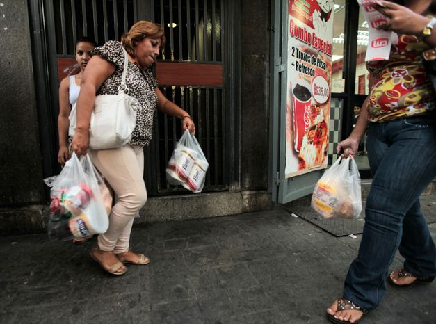 ** FILE ** A customer leaves a supermarket with her purchases, including toilet paper, which is in short supply, in Caracas, Venezuela, on Wednesday, May 15, 2013. Blaming political opponents for the shortfall, as it does for other shortages, the embattled socialist government said it would import 50 million rolls of toilet paper to boost supplies. (AP Photo/Fernando Llano)
