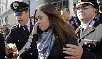 Karima el-Mahroug's is escorted outside the Milan's Law court by two Carabinieri police officers after giving her testimony at the trial of three former Berlusconi aides accused with procuring her and other woman for prostitution, in Milan, Italy, Friday, May 17, 2013. Silvio Berlusconi's private disco featured not only aspiring show girls performing striptease acts as sexy nuns and nurses, but also dressed as President Barack Obama. (AP Photo/Luca Bruno)
