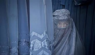A woman peers through the the eye slit of her burqa in Kabul, Afghanistan, April 11, 2013. (AP Photo/Anja Niedringhaus, File) ** FILE **