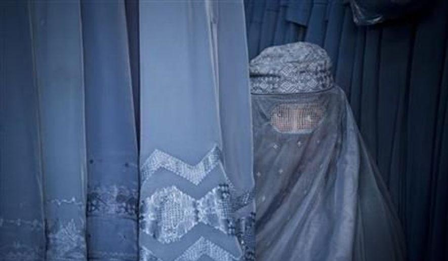 A woman peers through the the eye slit of her burqa in Kabul, Afghanistan, April 11, 2013. (AP Photo/Anja Niedringhaus, File) ** FILE **