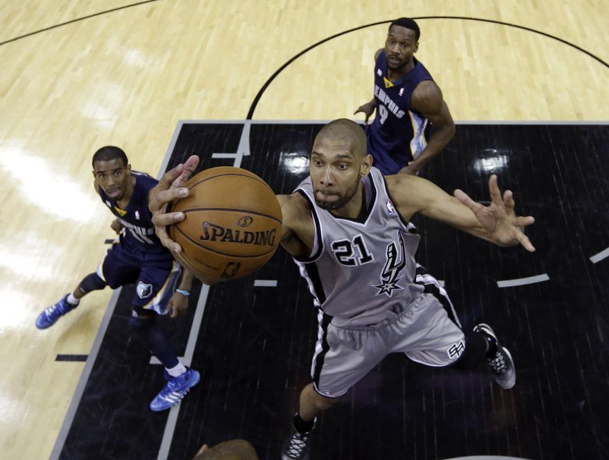 San Antonio Spurs' Tim Duncan (21) grabs a rebound as Memphis Grizzlies' Mike Conley (11) and Tony Allen (9) look on during the first half in Game 1 of a Western Conference Finals NBA basketball playoff series, Sunday, May 19, 2013, in San Antonio. (AP Photo/Eric Gay)