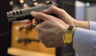 **FILE** The Smith & Wesson .45 caliber M1911pistol is held at the 35th annual SHOT Show in Las Vegas on Jan. 15, 2013. (Associated Press)