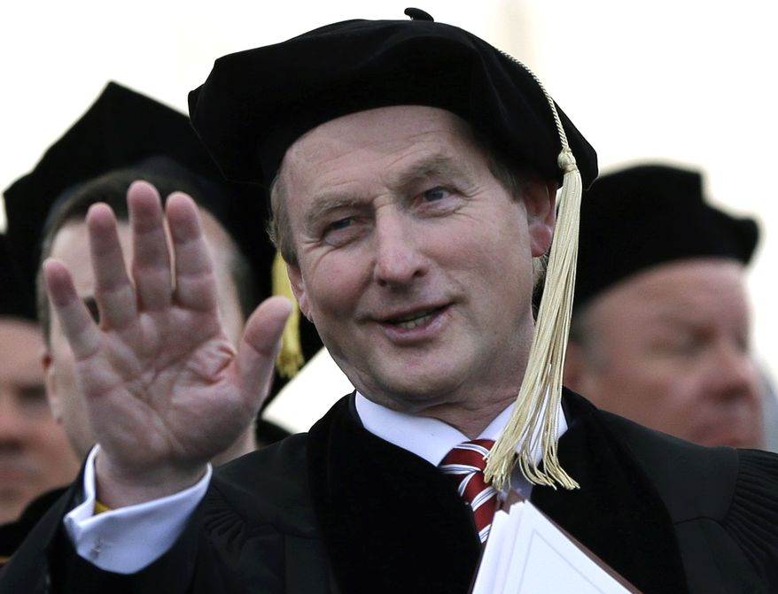 Irish Prime Minister Enda Kenny waves to students from the dais at Boston College, from which he received an honorary degree during commencement ceremonies at Alumni Stadium in Chestnut Hill, Mass., on Monday, May 20, 2013. Cardinal Sean O'Malley, who as archbishop of Boston traditionally would have given the benediction at the ceremony, skipped the event because of the involvement of Mr. Kenny, who supports a bill in his country that would allow abortion. (AP Photo/Elise Amendola)