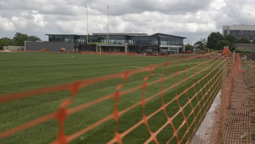 Workers continue the construction of the new Washington Redskins training facility in Richmond, Va., Monday, May 20, 2013. Sod was laid on the field last week. (AP Photo/Steve Helber)