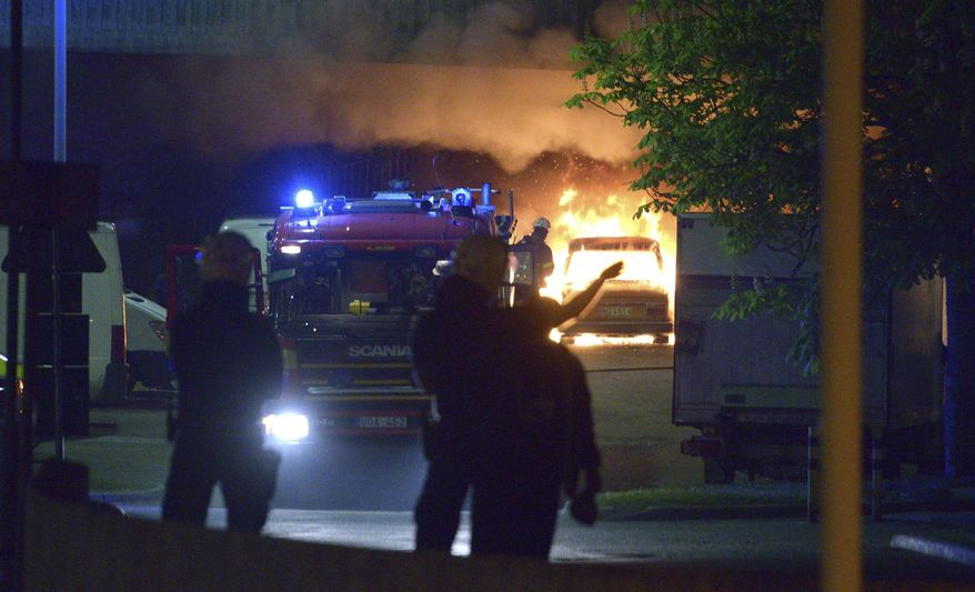Police officers stand guard in a street during a riot in Stockholm, Sweden, Monday, May 20, 2013. Gangs of youth apparently angered by the police shooting death of an elderly man hurled rocks at police and set cars and buildings on fire in a Stockholm suburb, forcing the evacuation of an apartment block. (AP Photo Johan Nilsson)