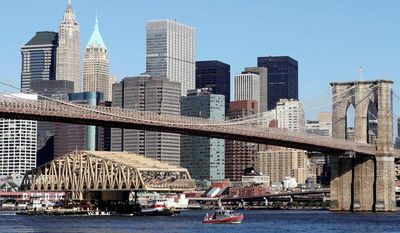 ** FILE ** The new Willis Avenue Bridge passes under the Brooklyn Bridge as it is brought up the East River on a barge in New York on Monday. The bridge is replacing the existing 109-year-old span that connects Upper Manhattan and the South Bronx. (Associated Press)