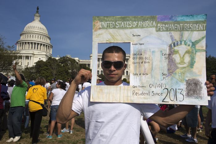 """**FILE** Roberto Morales, 25, holds a sign representing a permanent resident card while attending the """"Rally for Citizenship"""" on Capitol Hill on April 10, 2013, in support of immigration reform. (Associated Press)"""
