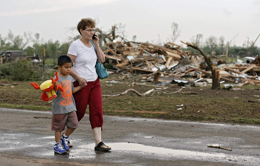 Chole Findley walks with her grandson Mark Williams as they leave the area where their home was destroyed after the tornado hit the area near 149th and Drexel on Monday, May 20, 2013 in Oklahoma City, Okla. (AP Photo/ The Oklahoman, Chris Landsberger)