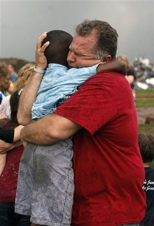 A teacher hugs a child at Briarwood Elementary school after a tornado destroyed the school in south Oklahoma City, Monday, May 20, 2013. A monstrous tornado roared through the Oklahoma City suburbs, flattening entire neighborhoods with winds up to 200 mph, setting buildings on fire and landing a direct blow on an elementary school. (AP Photo/The Oklahoman, Paul Hellstern)