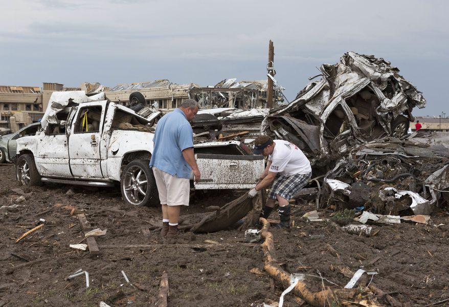 Two men go through the damage surrounding the Moore Medical Center after a tornado moves through Moore, Okla., on Monday, May 20, 2013. (AP Photo/Alonzo Adams)