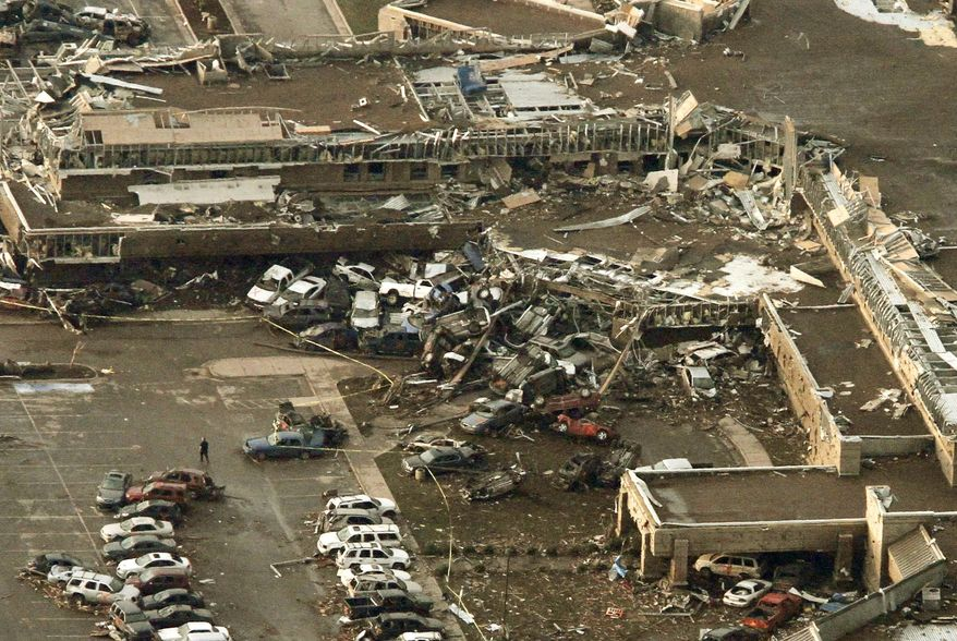 Emergency crews recover a body from the 7-Eleven store at the corner of Telephone Road and SW 4th Street after a tornado in Moore, Okla., on Monday, May 20, 2013. (AP Photo/Alonzo Adams)