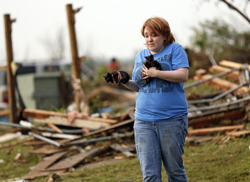 Rachel Hilton holds stray kittens she found in the debris of her parents' home at SW 149th and Stone Meadows Drive after a tornado struck south Oklahoma City and Moore, Okla., Monday, May 20, 2013. (AP Photo/The Oklahoman, Nate Billings)