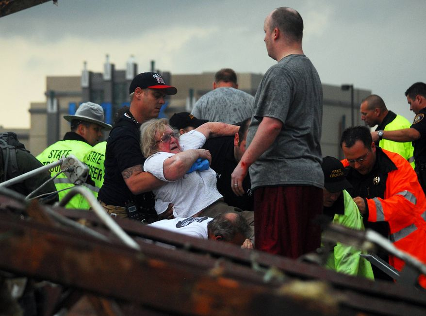 Emergency workers pull out a woman that was trapped in a building that was destroyed off of 4th Street and Interstate 35 after a tornado ripped through Moore, Okla., Monday May 20, 2013. (AP Photo/ The Transcript, Kyle Phillips )