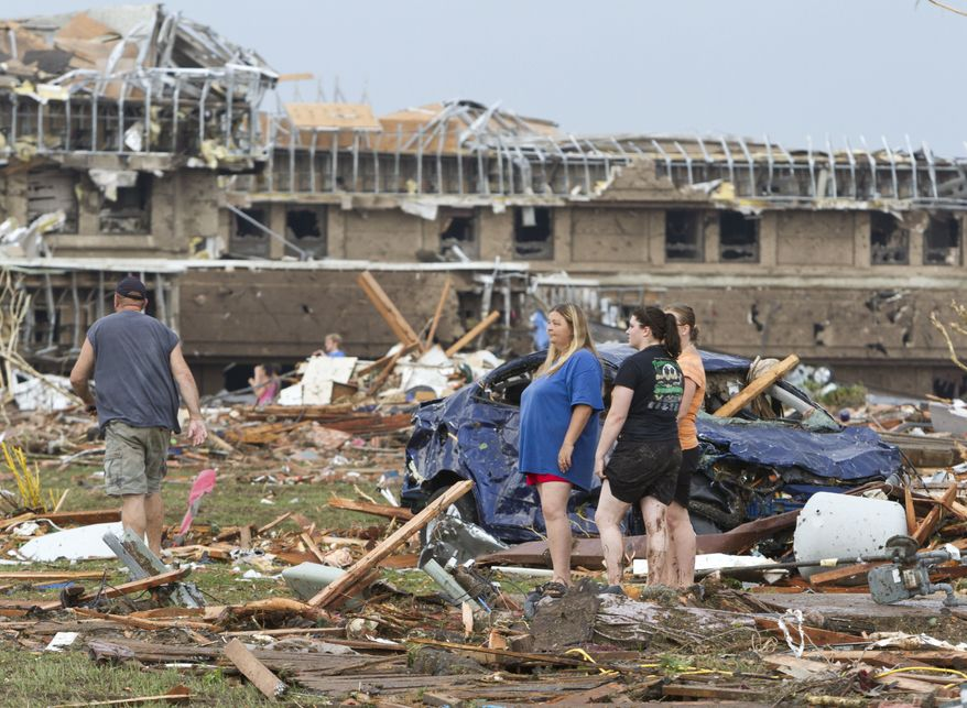 People go through the debris near Telephone Road and SW 4th Street after a tornado moves through Moore, Okla., on Monday, May 20, 2013. (AP Photo/Alonzo Adams)