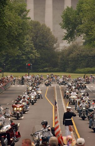 Motorcyclists receive a salute as the Rolling Thunder contingent passes near the Lincoln Memorial on the final leg of their journey as crowds gather on sidewalks to wave. (The Washington Times)