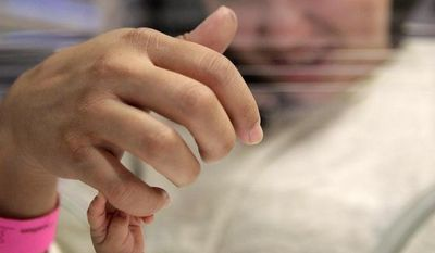 Fourteen-week-old Melinda Star Guido holds her mother's little finger while lying in an incubator at the Los Angeles County-USC Medical Center in Los Angeles, Wednesday, Dec. 14, 2011. (AP Photo/Jae C. Hong)
