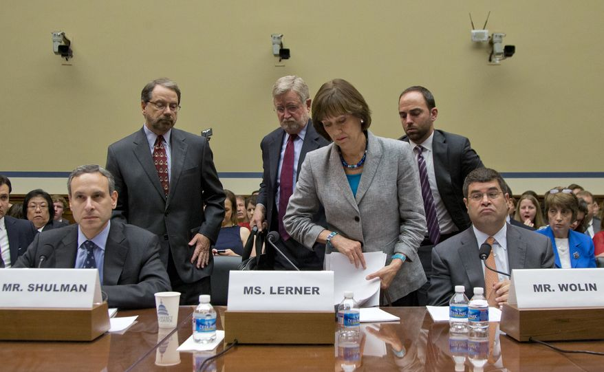 IRS official Lois Lerner leaves a House Oversight Committee hearing on Capitol Hill in Washington on Wednesday, May 22, 2013. Ms. Lerner told the committee she did nothing wrong and then invoked her constitutional right to not answer lawmakers' questions. At left is former IRS Commissioner Douglas Shulman; at right is Deputy Secretary of the Treasury Neal S. Wolin. (AP Photo/Carolyn Kaster)
