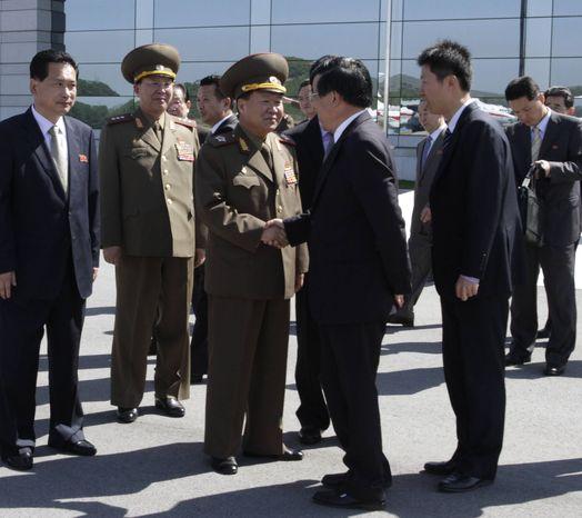 High-ranking North Korean party and military official Choe Ryong Hae, center left, shakes hands with Chinese Ambassador Liu Hongcai as Choe departs for China as a special envoy of North Korean leader Kim Jong-un, at Pyongyang airport, North Korea Wednesday, May 22, 2013. (AP Photo/ Kim Kwang Hyon)