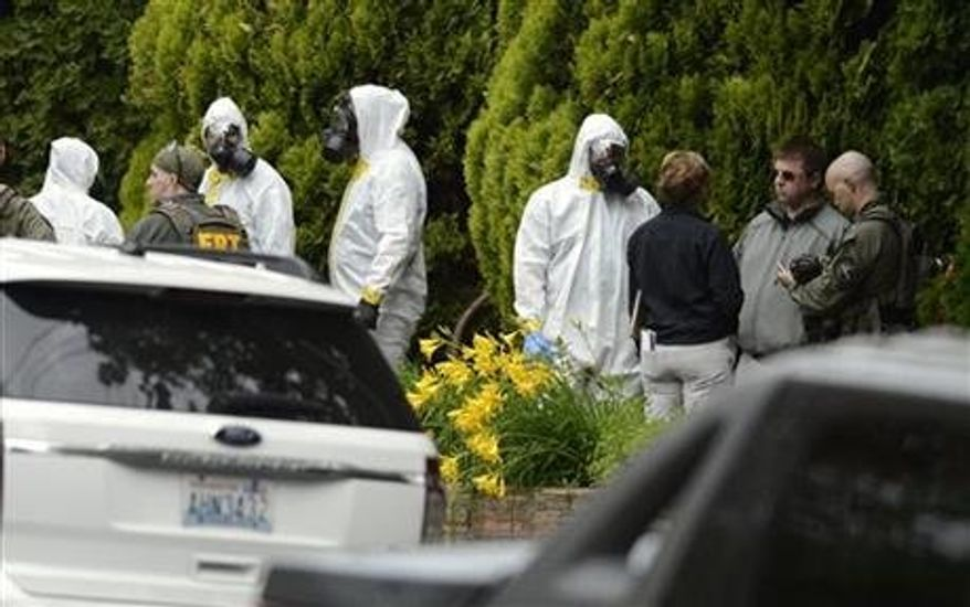 During the execution of a search warrant, members of the Joint Federal Haz-Mat Team, FBI, and local law enforcement gather in front of the Osmun Apartments near the intersection of First Avenue and Oak Street in Browne's Addition on Saturday, May 18, 2013 in Spokane, Wash. The search warrant is in connection with ricin-laced letters intercepted at a Post Office facility in Spokane earlier in the week. (Associated Press)