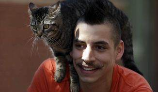 In this Tuesday, May 21, 2013, photo, bicyclist Rudi Saldia and his cat Mary Jane pose for a portrait during an interview with The Associated Press in Philadelphia. (AP Photo/Matt Rourke)