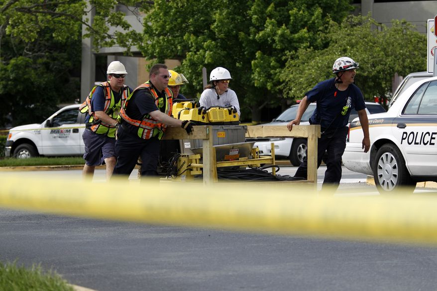 Montgomery County fire and rescue members move equipment as they try to rescue a worker severely injured who is trapped in the partial collapsed parking garage at Montgomery Mall in Bethesda , Md., Thursday, May 23, 2013. Officials say it appears a 50,000-pound section of the parking deck collapsed outside a Macy's store. Fire Department spokeswoman Beth Anne Nesselt says one man died. The second worker has serious and potentially life-threatening injuries. (AP Photo/Jose Luis Magana)