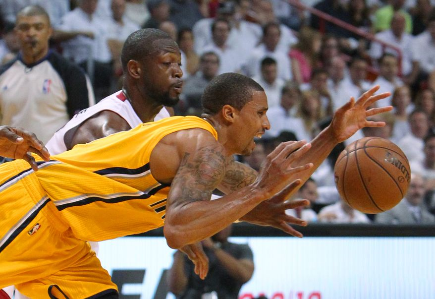Miami Heat guard Dwyane Wade battles for a lose ball against Indiana Pacers guard George Hill during the third quarter of Game 1 in the NBA Eastern Conference Finals between the Indiana Pacers against the Miami Heat in Miami on Wednesday, May 22, 2013. (AP Photo/Miami Herald, C.W. Griffin)