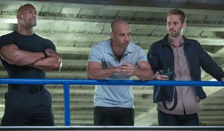 "Dwayne ""The Rock"" Johnson, left, Vin Diesel, center, and Paul Walker in a scene from ""Fast & Furious 6."" (AP Photo/Universal Pictures, Giles Keyte)"