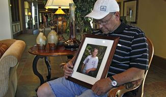 Marvin Dixon, the grandfather of 8-year-old tornado victim Kyle Davis, glances down at a photo of his grandson while sitting for a portrait in the lobby of a funeral home where his grandson awaits burial, in Oklahoma City, Wednesday, May 22, 2013. (AP Photo/Brennan Linsley)
