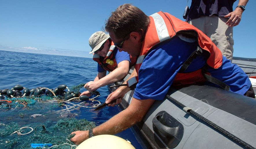 ** FILE ** This Aug. 11, 2009, file photo provided by the Scripps Institution of Oceanography shows Matt Durham, center, pulling in a large patch of sea garbage with the help of Miriam Goldstein, right, in the Pacific Ocean. Plastics discarded by people often end up in the ocean, creating coastal pollution that harms marine life and gathers out at sea in what's become known as the great Pacific garbage patch. Now, California state lawmakers have introduced a law that if passed would require makers of plastic bottles, bags and packaging to replace plastics with more environmentally friendly alternatives. (AP Photo/ Scripps Institution of Oceanography, Mario Aguilera, File)