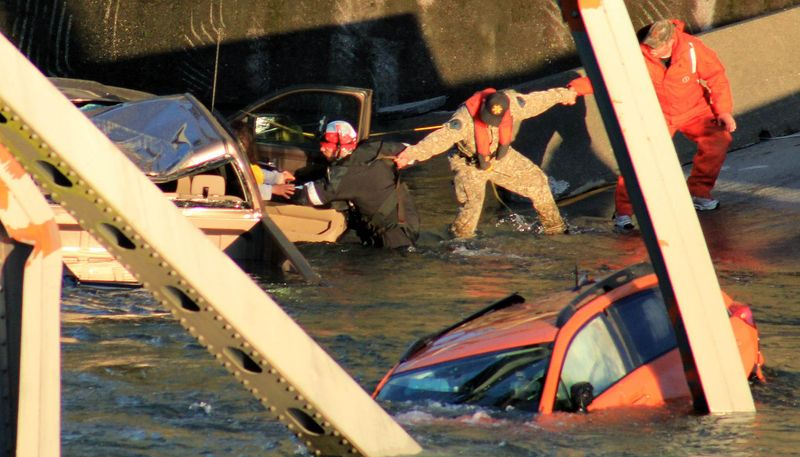 In this photo provided by Francisco Rodriguez, rescue workers form a human chain as they begin to remove a woman who reaches out from a smashed pickup truck that fell into the Skagit River after the collapse of the Interstate 5 bridge on Thursday, May 23, 2013, in Mount Vernon, Wash. (AP Photo/Francisco Rodriguez)