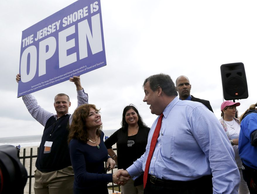 ** FILE ** New Jersey Gov. Chris Christie, right, talks to Carla Pilla, of Seaside Heights, N.J., while Robert Hilton, left, executive director of the Jersey Shore Convention and Visitor's Bureau, holds a sign, Friday, May 24, 2013, in Seaside Heights, N.J. Christie cut a ribbon to symbolically reopen the state's shore for the summer season, seven months after being devastated by Superstorm Sandy. (AP Photo/Julio Cortez)