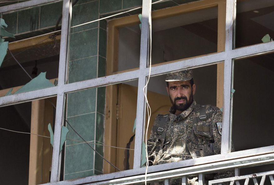 ** FILE ** An Afghan Army soldier peers through a destroyed shop window at the scene where a suicide car bomber attacked a NATO convoy in Kabul, Afghanistan, Thursday, May 16, 2013. A Muslim militant group, Hizb-e-Islami, claimed responsibility for the early morning attack, killing many in the explosion and wounding tens, police and hospital officials said. (AP Photo/Anja Niedringhaus)