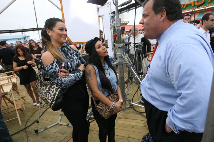 """**FILE** New Jersey Gov. Christie speaks with Nicole """"Snooki"""" Polizzi, center, and Jenni """"JWoww"""" Farley, cast members of MTV's """"Jersey Shore,"""" on the boardwalk where he took part in a ribbon-cutting ceremony to reopen the beach in Seaside Heights, N.J., on May 24, 2013. (Associated Press/Northjersey.com, Kevin R. Wexler)"""