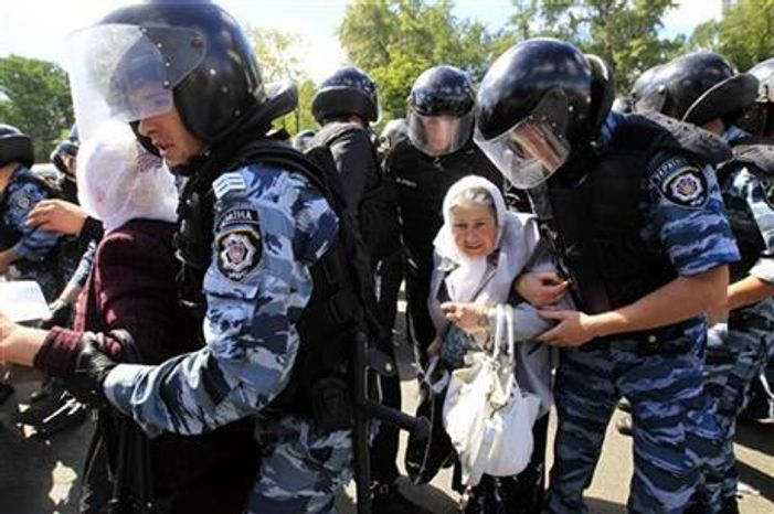 Riot police stop Orthodox protesters who are trying to stop Ukraine's first gay pride demonstration in Kiev, Ukraine, Saturday, May 25, 2013. (AP Photo/Sergei Chuzavkov)