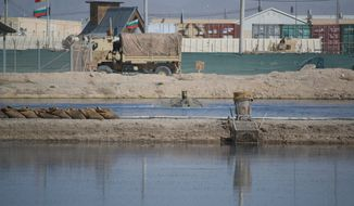 "The iconic ""Poo Pond,"" a waste retention pond at the Kandahar Air Field known for its odor, was slated to close mid-2013. However, the pond, shown here in this May 17, 2013, photo, will remain open until the airfield's residents no longer need a place to discard waste, including that from portable toilets. (Kristina Wong/The Washington Times)"