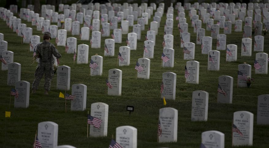 "A soldier with the 3rd U.S. Infantry Regiment, also known as ""The Old Guard,"" places flags at grave sites at Arlington National Cemetery in Arlington, Va., on Thursday, May 23, 2013, as part of the annual ""Flags-In"" ceremony in preparation for Memorial Day. (AP Photo/Evan Vucci)"
