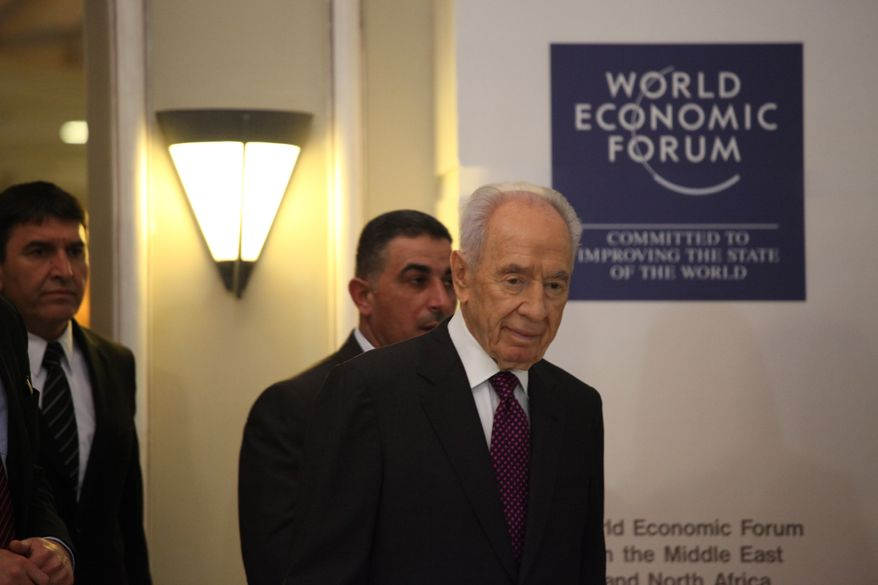 Israeli President Shimon Peres (right) arrives to give a brief statement at the World Economic Forum in Southern Shuneh, Jordan, on Sunday, May 26, 2013. Mr. Peres says that it is possible for Israelis and Palestinians to overcome differences and skepticism over peacemaking and that it is time to restart serious negotiations and conclude a peace treaty that long has dogged the two warring sides. (AP Photo/Mohammad Hannon)
