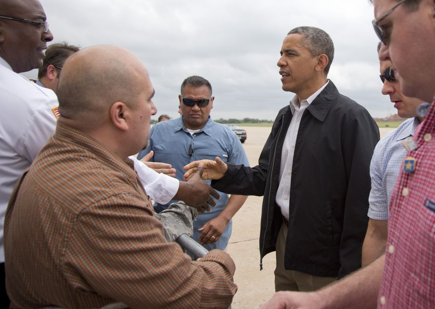 President Obama greets people on the apron as he arrives on Sunday, May 26, 2013, at Tinker Air Force Base in Midwest City, Okla., en route to the Moore, Okla., to see the response efforts to the severe tornadoes and weather that devastated the area. He will also visit with the families affected as well as first responders. (AP Photo/Carolyn Kaster)