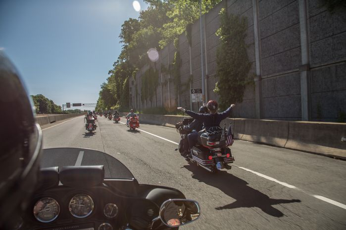 Washington Times Reporter, Meredith Somers, holds her arms out as she is rides down interstate 66, during the annual Ride of the Patriots, in support of Rolling Thunder, in Fairfax, VA., Sunday, May 26, 2013.  (Andrew S Geraci/The Washington Times)