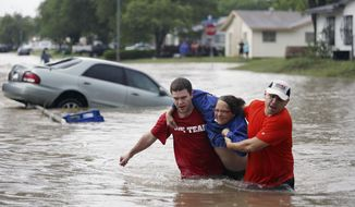 Marco Fairchild (left) and Gary Garza (right) help Sueann Schaller from her car on Saturday, May 25, 2013, in San Antonio after she drove it into floodwaters in the Westwood Village neighborhood. (AP Photo/San Antonio Express-News, Lisa Krantz)