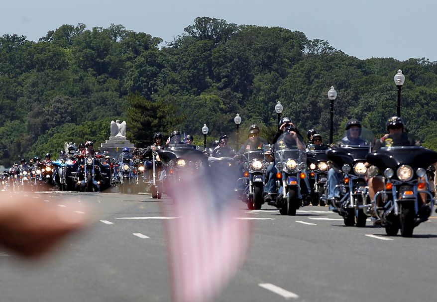 """Motorcycles drive over the Memorial Bridge during the annual Rolling Thunder """"Ride for Freedom"""" parade ahead of Memorial Day in Washington, Sunday, May 26, 2013. (AP Photo/Molly Riley)"""