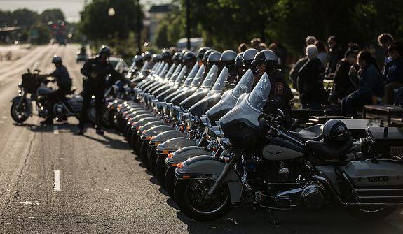 Fairfax county motorcycle police park their bikes in a precise line, outside the Patriot Harley-Davidson in preparation to escort rides in the annual Ride of the Patriots, in support of Rolling Thunder, in Fairfax, VA., Sunday, May 26, 2013.  (Andrew S Geraci/The Washington Times)