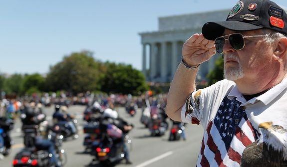 "Ken Caryl of Dale City, Va. salutes the motorcyclists, many of them are veterans, as they ride across the Memorial Bridge into Washington Sunday, May 26, 2013, during the annual Rolling Thunder ""Ride for Freedom"" parade ahead of Monday's Memorial Day celebration. (AP Photo/Molly Riley)"